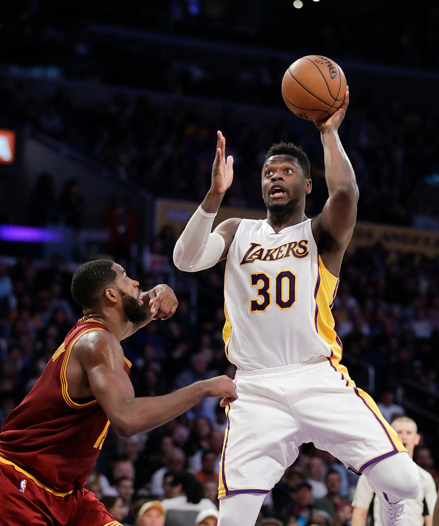 . Los Angeles Lakers\' Julius Randle, right, shoots over Cleveland Cavaliers\' Tristan Thompson during the first half of an NBA basketball game Sunday, March 19, 2017, in Los Angeles. (AP Photo/Jae C. Hong)