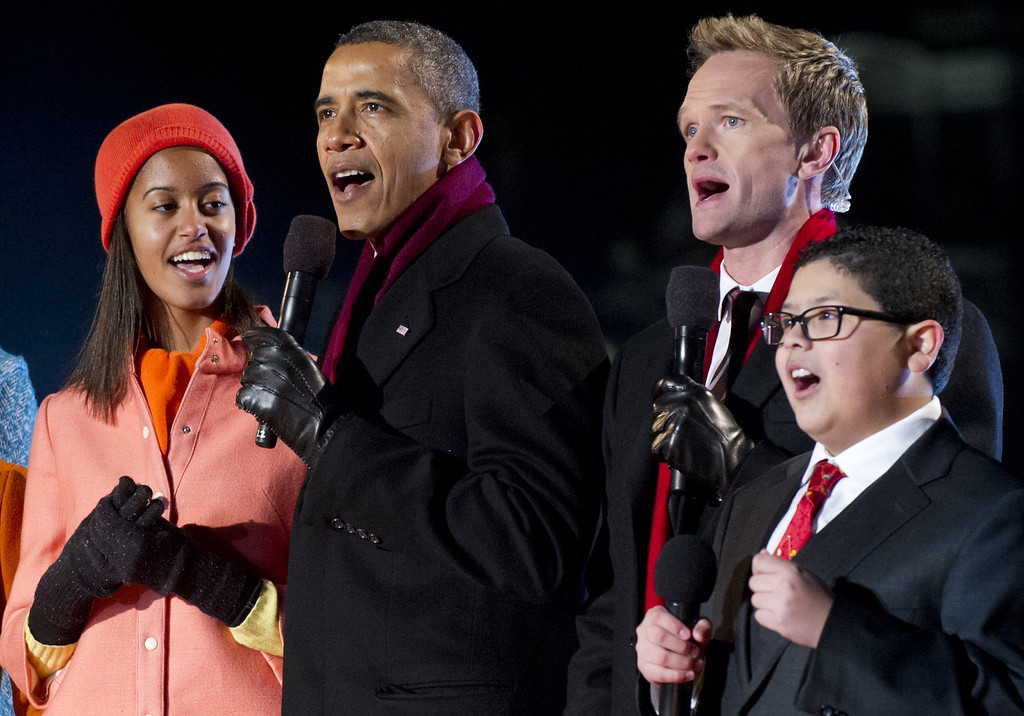 ". US President Barack Obama (2nd L) alongside his daughter Malia (L), sing with actor Neil Patrick Harris (2nd R) and actor Rico Rodriguez (R) from the televison show ""Modern Family\"" during the National Christmas Tree Lighting on the Ellipse adjacent to the White House in Washington, DC, on December 6, 2012. The annual event, hosted by Harris, features US President Barack Obama and performances by Jason Mraz, Ledisi, James Taylor, Kenny \""Babyface\"" Edmonds, Colbie Caillat and American Idol season 11 winner Phillip Phillips.  SAUL LOEB/AFP/Getty Images"