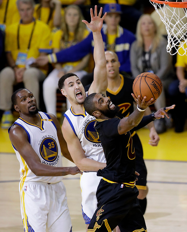 . Cleveland Cavaliers guard Kyrie Irving, right, shoots past Golden State Warriors forward Kevin Durant (35) and guard Klay Thompson during the second half of Game 2 of basketball\'s NBA Finals in Oakland, Calif., Sunday, June 4, 2017. (AP Photo/Marcio Jose Sanchez)