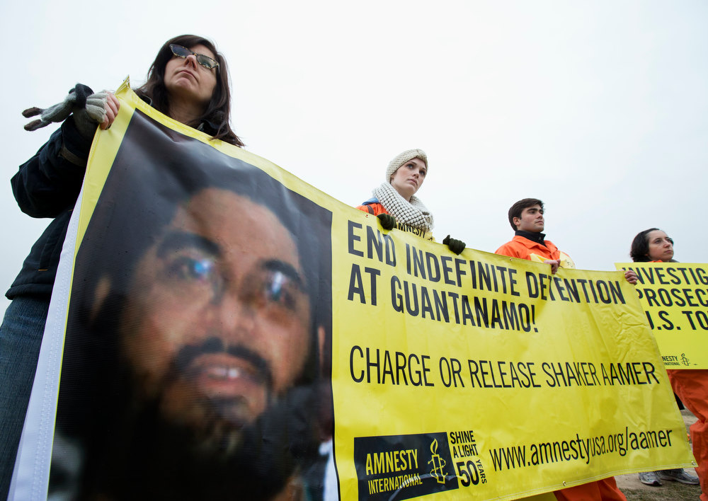 Description of . Human rights activists from left, Michelle Ringuette, Kelly Mitchell, Felipe Pereira and Rebecca Elliott, hold a banner with a picture of Saudi national Guantanamo detainee Shaker Aamer, during a rally near the Ellipse, near the White House in Washington, Friday, Jan. 11, 2013. The rally marked the 11th anniversary of the first detainees being jailed at the U.S.-controlled detention facility in Guantanamo Bay, calling on President Barack Obama to close Guantanamo.   (AP Photo/Manuel Balce Ceneta)