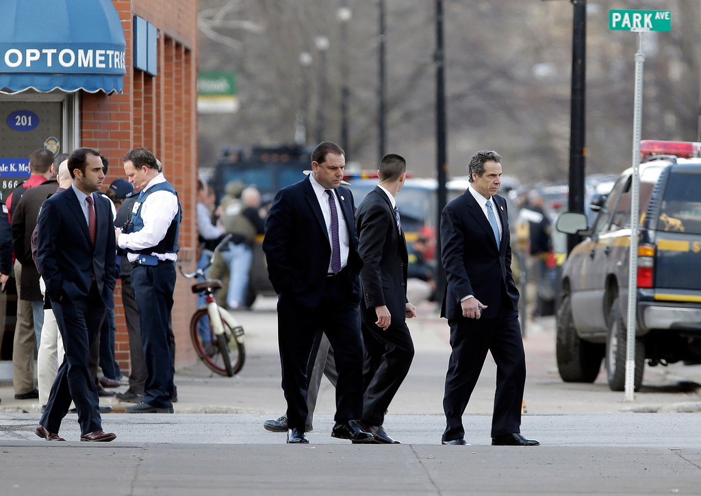 . New York Gov. Andrew Cuomo, right, walks to a vehicle as law enforcement officers take cover along Main Street after shots were fired while they were searching for a suspect in two shootings that killed four and injured at least  two on, Wednesday, March 13, 2013, in Herkimer, N.Y.(AP Photo/Mike Groll)
