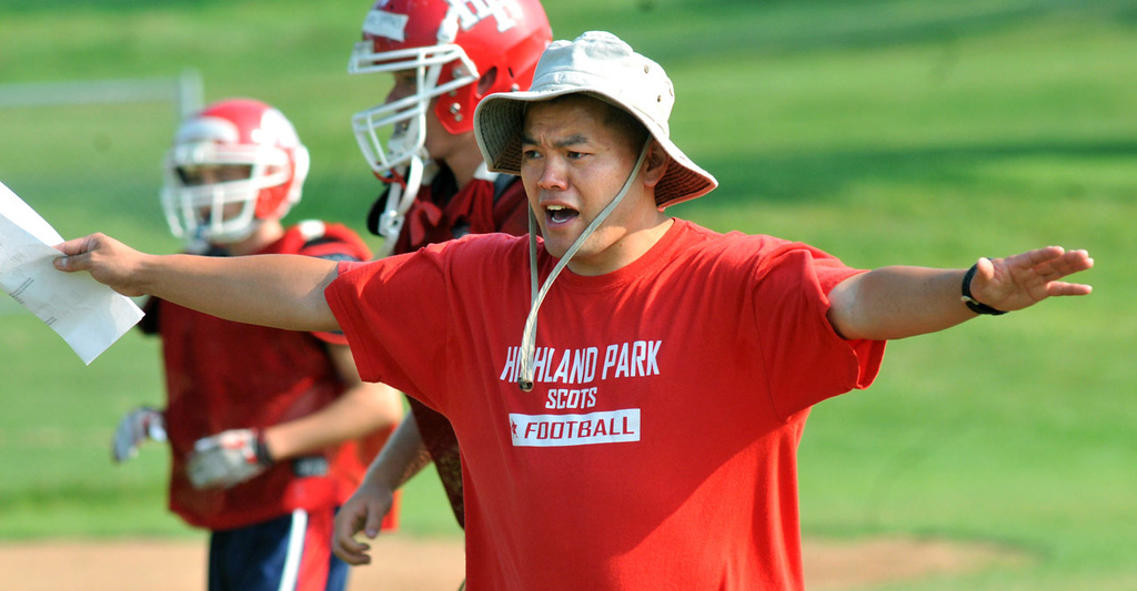 . Highland Park assistant coach Elliott Vang shouts instructions to his players during practice at Highland Park High School in St. Paul on Tuesday, August 20, 2013. Vang is the only Hmong high school football coach in the St. Paul City Conference.  (Pioneer Press: John Doman)
