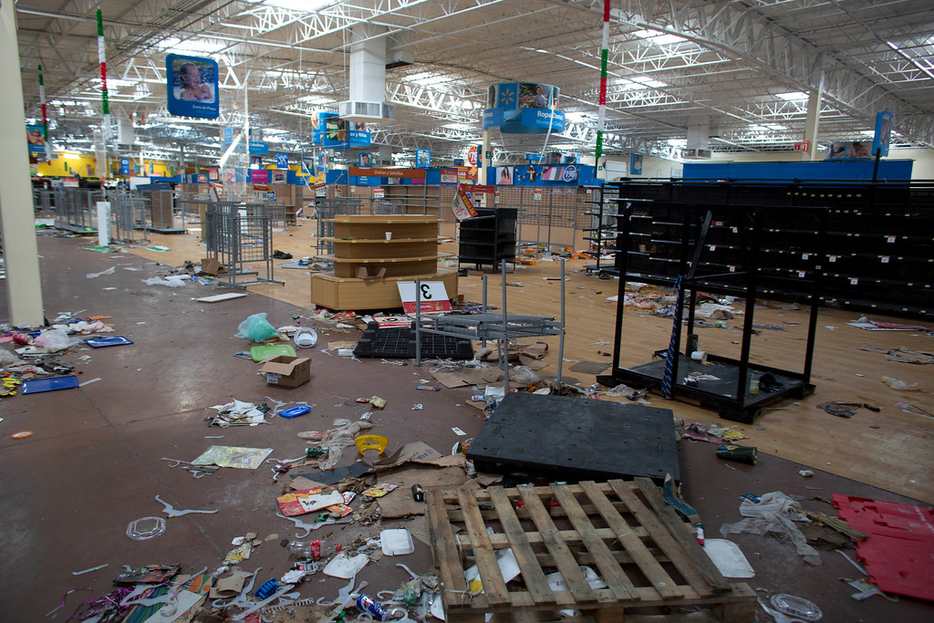 """. Debris litters the floor of a Wal-Mart superstore that was damaged and then looted after the passing of Hurricane Odile in San Jose de los Cabos, Mexico, Wednesday, Sept. 17, 2014. Inside the waterlogged Wal-Mart superstore, there was nothing but puddles, trash, empty shelves and graffiti on the wall that read: \""""Long live crime!\"""" (AP Photo/Dario Lopez-Mills)"""