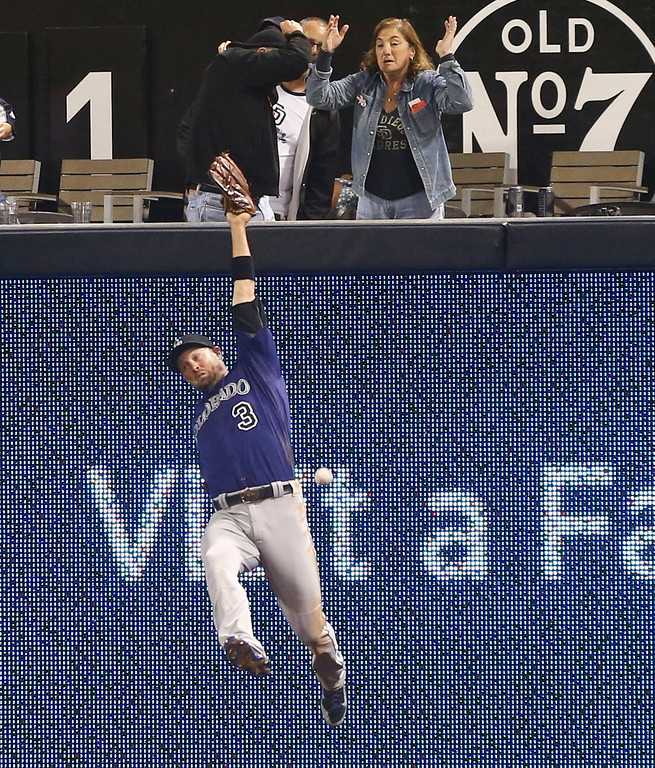. Colorado Rockies right fielder Michael Cuddyer can\'t make the catch on a deep drive by San Diego Padres\' Alexi Amarista in the fifth inning of a baseball game Monday, April 14, 2014, in San Diego.  Cuddyer could not make the catch and Amarista got a triple on the play. (AP Photo/Lenny Ignelzi)