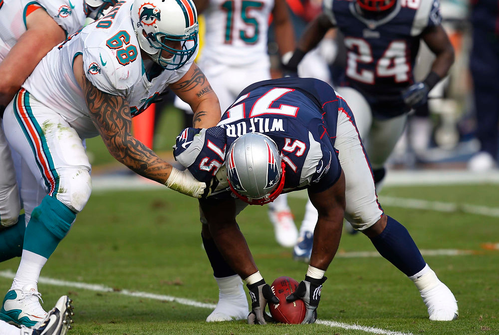 . New England Patriots defensive tackle Vince Wilfork (75) recovers the ball after Miami Dolphins quarterback Ryan Tannehill was sacked and fumbled the ball during the first half of an NFL football game, Sunday, Dec. 2, 2012, in Miami. Dolphins guard Richie Incognito is at left. (AP Photo/Wilfredo Lee)