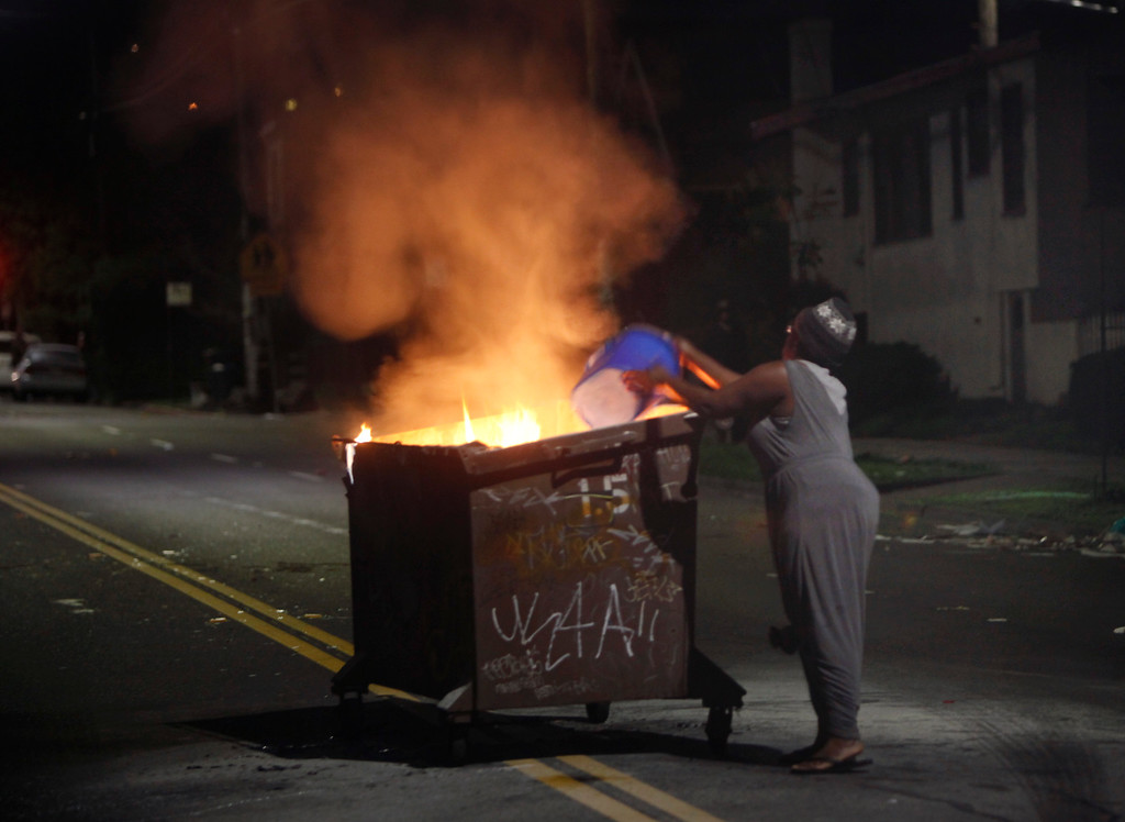 """. Ashby Avenue resident Janine Jenkins uses a bucket of water to extinguish a burning trash bin left in the middle of her street by protesters in Berkeley, Calif., late Sunday evening, Dec. 7, 2014. \""""Protesting is a great tool,\"""" she said, pointing to her litter-strewn street and vandalized antique store neighbor, \""""but who wants to wake up to this.\"""" (Karl Mondon/Bay Area News Group)"""