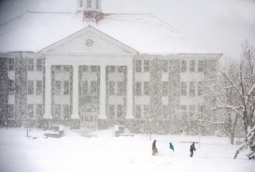 . Three people walk the James Madison University Quad, with Wilson Hall pictured in the background, during the snow storm Wednesday morning, March 6, 2013 in Harrisonburg, Va. (AP Photo/Daily News-Record, Nikki Fox)