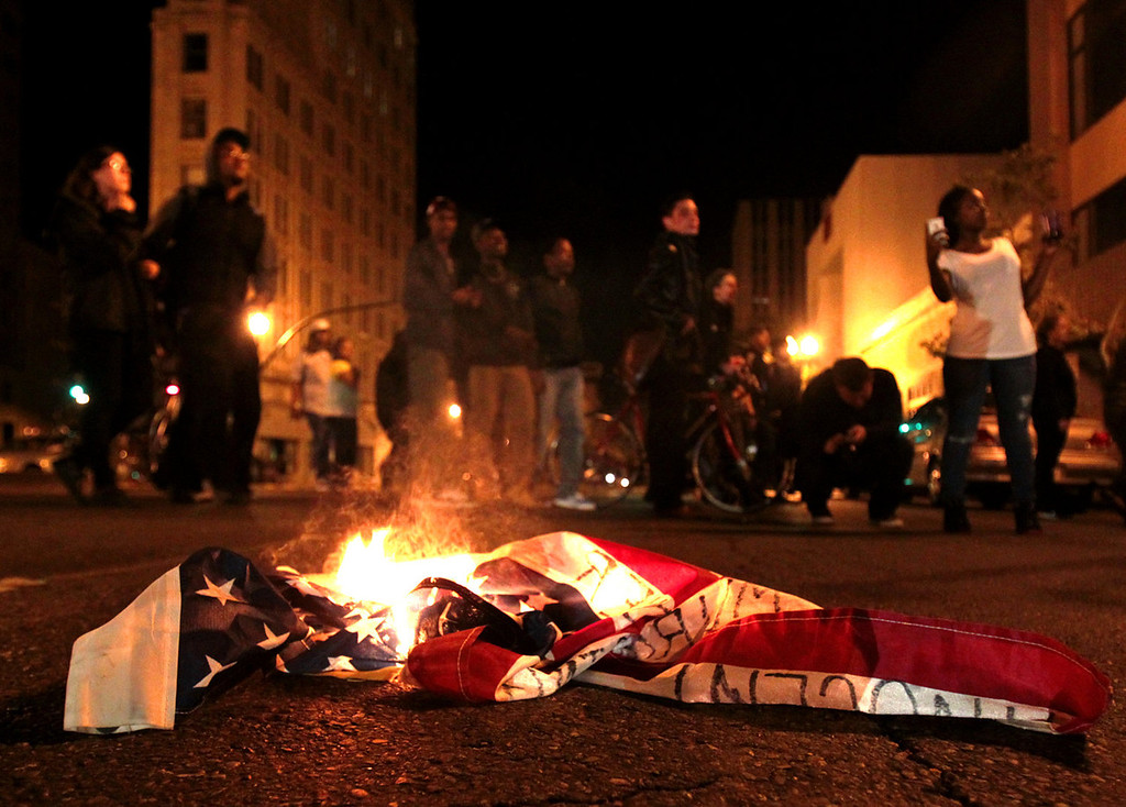 . A flag burns during a protest after George Zimmerman was found not guilty in the 2012 shooting death of teenager Trayvon Martin, early Sunday, July 14, 2013, in Oakland, Calif. Protesters angered by the acquittal Zimmerman held largely peaceful demonstrations in three California cities, but broke windows and started small street fires Oakland, police said. (AP Photo/Bay Area News Group, Anda Chu)