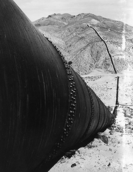 ". View showing one of the ""sag pipes\"" of the Los Angeles Aqueduct in Jawbone Canyon. The aqueduct is based on gravity flow that does not require pumping or siphoning, instead water is conveyed via pressure developed in the down slope to force the water through the up slope. Jawbone Canyon is located just west of Highway 14, south of Randsburg Red Rock Road in Kern County. This section of the aqueduct, built in 1913, was designed by William Mulholland.   (1955) (Los Angeles Public Library)"