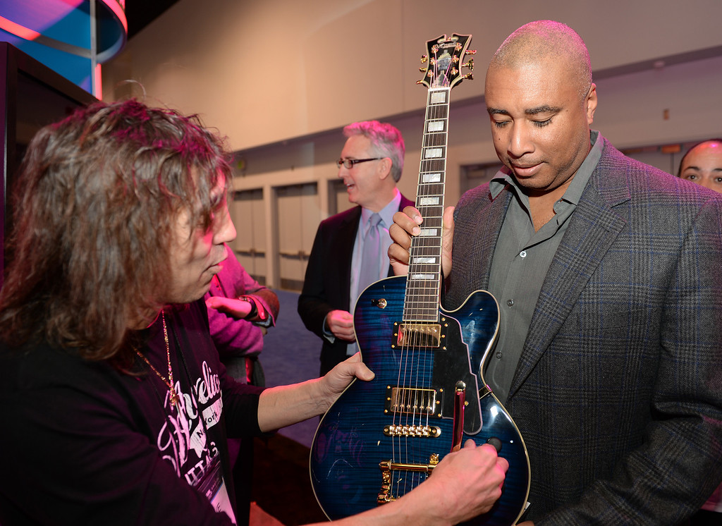 . Former New York Yankee Bernie Williams, right receives his custom made guitar from Steve Pisani, left, from D\'Angelico Guitars during the Media Preview event for the NAMM Show at the Anaheim Convention Center on Wednesday January 22, 2014. The NAMM Show, National Association of Music Merchants, is a trade-only event for the music products industry that is held every January. It is one of the two largest music product trade shows in the world. (Staff Photo by Keith Durflinger/San Gabriel Valley Tribune)