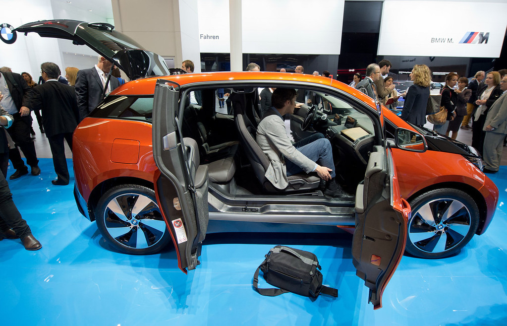 . Journalists view the i3 electric car by car manufacturer BMW at the Frankfurt Motor Show (IAA) in Frankfurt Main, Germany, Monday, Sept. 9, 2013. The 65th IAA runs Sept 12 through 22, 2013. (AP Photo/dpa, Boris Roessler)