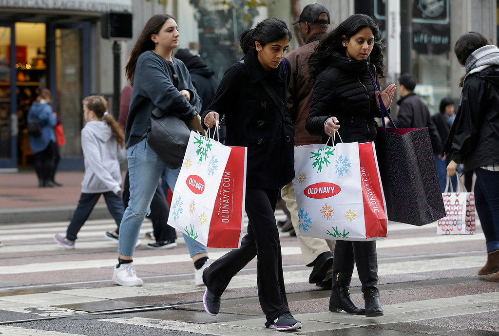 . Shoppers carry bags as they cross Market Street in San Francisco, Friday, Nov. 25, 2016. Black Friday, historically the starting line of the retail industry\'s crucial holiday buying season, isn\'t quite the one-day spree it used to be. Some retailers have pushed their biggest Black Friday door-buster deals into Thanksgiving Day and spread other promotions to even earlier in the season. (AP Photo/Jeff Chiu)
