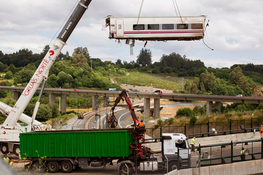 . A derailed train car is lifted by a crane at the site of a train accident in Santiago de Compostela, Spain, Thursday, July 25, 2013.  (AP Photo/Lalo Villar)