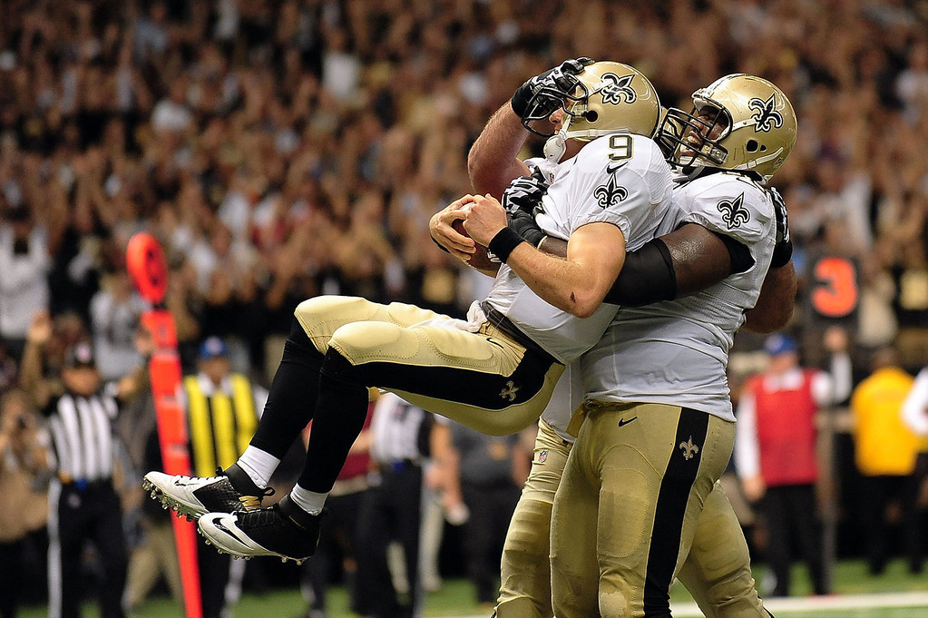 . Ben Grubbs #66 of the New Orleans Saints celebrates a touchdown with Drew Brees #9 during a game against the Arizona Cardinals at the Mercedes-Benz Superdome on September 22, 2013 in New Orleans, Louisiana.  The Saints defeated the Cardinals 31-7.  (Photo by Stacy Revere/Getty Images)