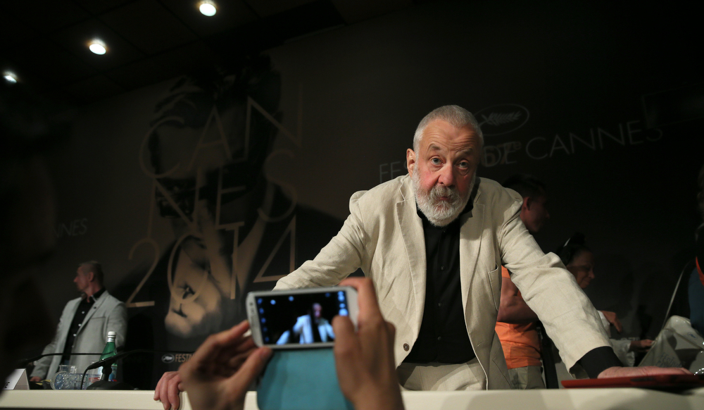 . Director Mike Leigh leans over a table as he speaks to journalists during a press conference for Mr. Turner at the 67th international film festival, Cannes, southern France, Thursday, May 15, 2014. (AP Photo/Alastair Grant)