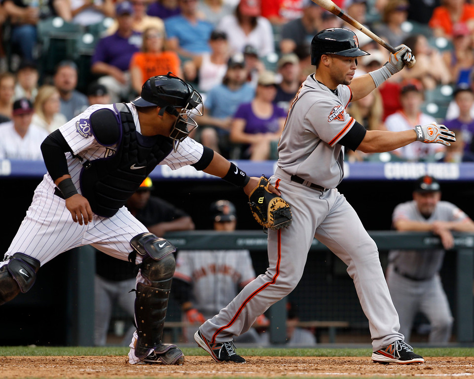 . Colorado Rockies catcher Yorvit Torrealba, left, tags out San Francisco Giants\' Juan Perez after he struck out while swinging at a pitch in the fifth inning of a baseball game in Denver on Saturday, June 29, 2013. Torealba had dropped the ball after the swing by Perez. (AP Photo/David Zalubowski)