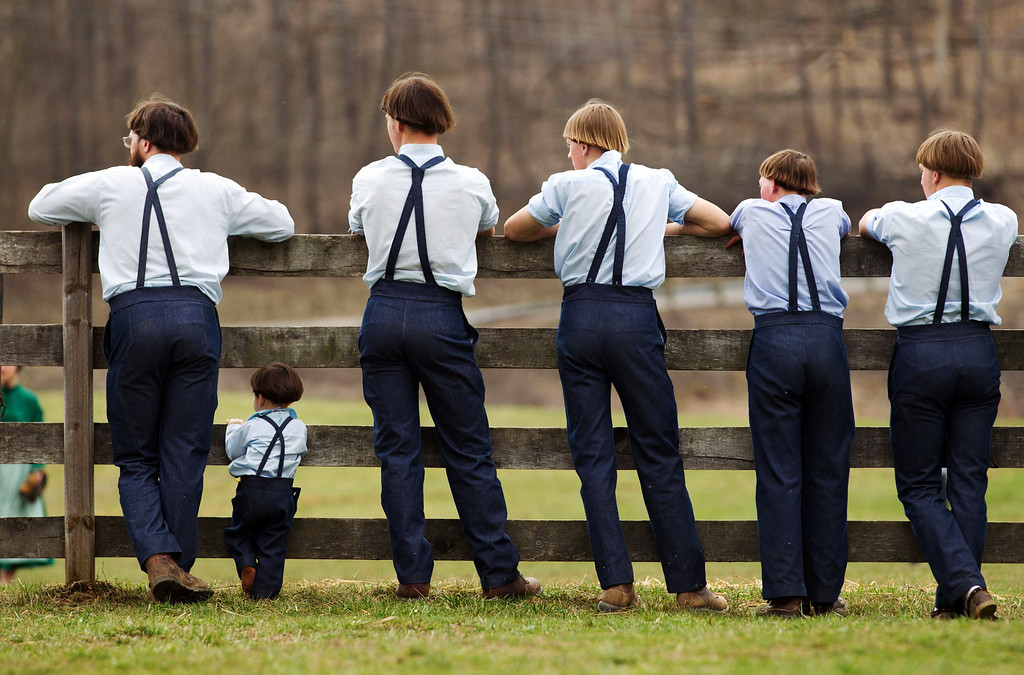 . Amish boys watch a game of baseball outside the school house in Bergholz, Ohio, on Tuesday, April 9, 2013.  Many Amish families gathered following the final day of school for a celebration and farewell picnic. (AP Photo/Scott R. Galvin, File)