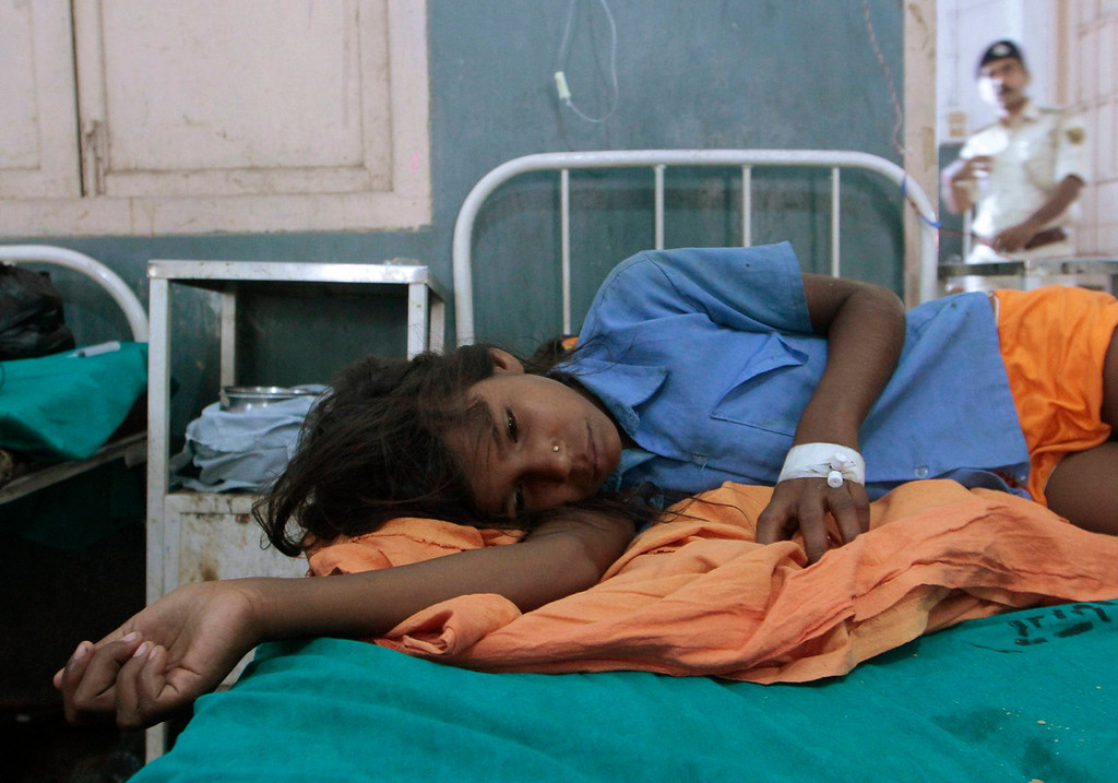 . A sick girl rests at a hospital after consuming contaminated school meals in the eastern Indian city of Patna July 17, 2013. At least 22 children died and dozens were taken to hospital with apparent food poisoning after eating a meal provided for free at their school in the Indian state of Bihar, officials said on Wednesday, sparking violent protests. REUTERS/Stringer
