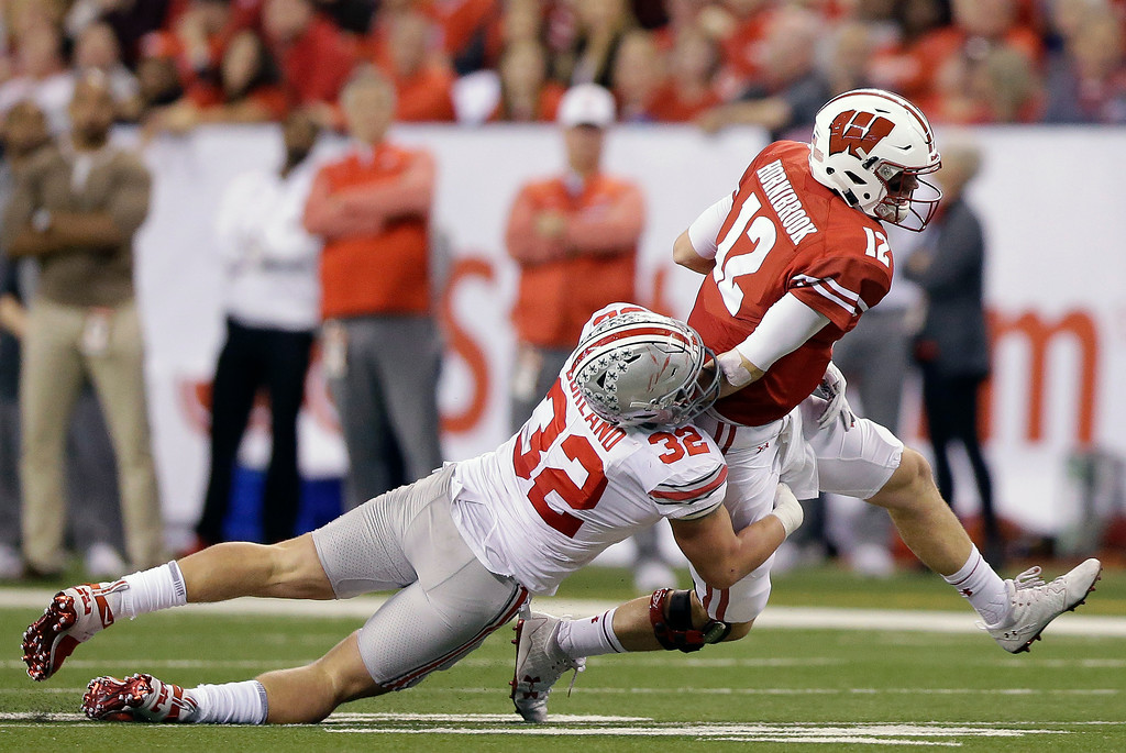 . Wisconsin quarterback Alex Hornibrook (12) is tackled by Ohio State\'s Tuf Borland (32) during the first half of the Big Ten championship NCAA college football game, Saturday, Dec. 2, 2017, in Indianapolis. (AP Photo/AJ Mast)