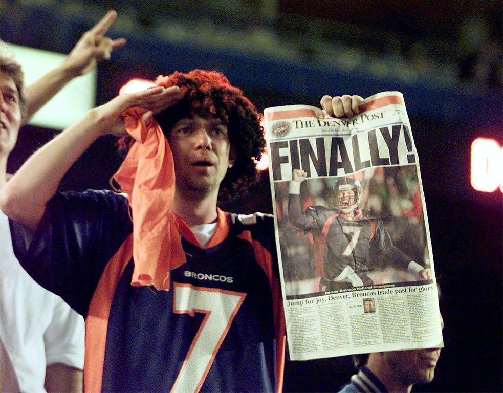 . A unidentified fan holds up a Denver Post at the end of  Super Bowl XXXII in San Diego as the Denver Broncos beat the  Green Bay Packers. (Kent Meireis/The Denver Post)