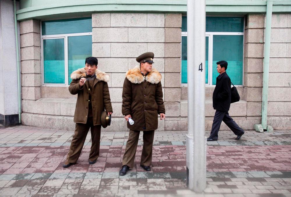 Description of . Two North Korean soldiers smoke cigarettes as a pedestrian walks past on a street corner in Pyongyang, North Korea on Friday April 22, 2011.  (AP Photo/David Guttenfelder)
