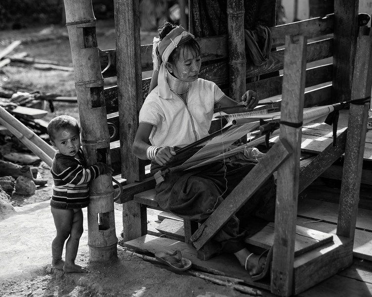 A woman from the kayan tribe weaving whilst watching over her little boy.   Kayah State, Myanmar, 2017