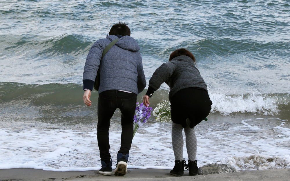 . Employees of a nursing home Tsutomu Sato, 34, left, and Yoko Katayama, 30, toss bouquets of flowers into the sea in remembrance of the 36 people who died in the home during the March 11, 2011 earthquake and tsunami in Minamisoma Fukushima Prefecture, northeastern Japan, Tuesday, March 11 2014. Japan on Tuesday marks the third anniversary of the March 11, 2011 earthquake and tsunami that killed 15,884 people and left more than 2,600 unaccounted for in vast areas of its northern coast.  (AP Photo/Koji Sasahara)