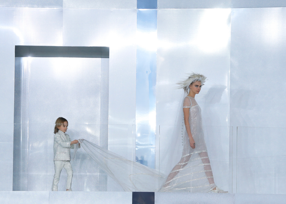 . Hudson Kroenig, 5, holds the wedding gown worn by model Cara Delevingne during Chanel\'s Spring-Summer 2014 Haute Couture fashion collection presented in Paris, Tuesday, Jan.21, 2014. (AP Photo/Jacques Brinon)