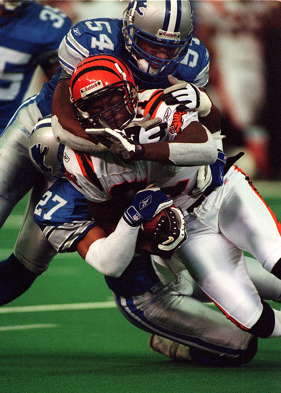 . Detroit Lions defenders Barrett Green (top) and Jimmy Wyrick (bottom) take down Cincinnati Bengal wide receiver Ron Dugans  during the Lions 31-27 loss at the Silverdome Sunday.