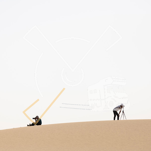 Perfect photography workshop image, almost cartoon like, from 2 tourist landscape photographers sitting on a sanddune photographing
