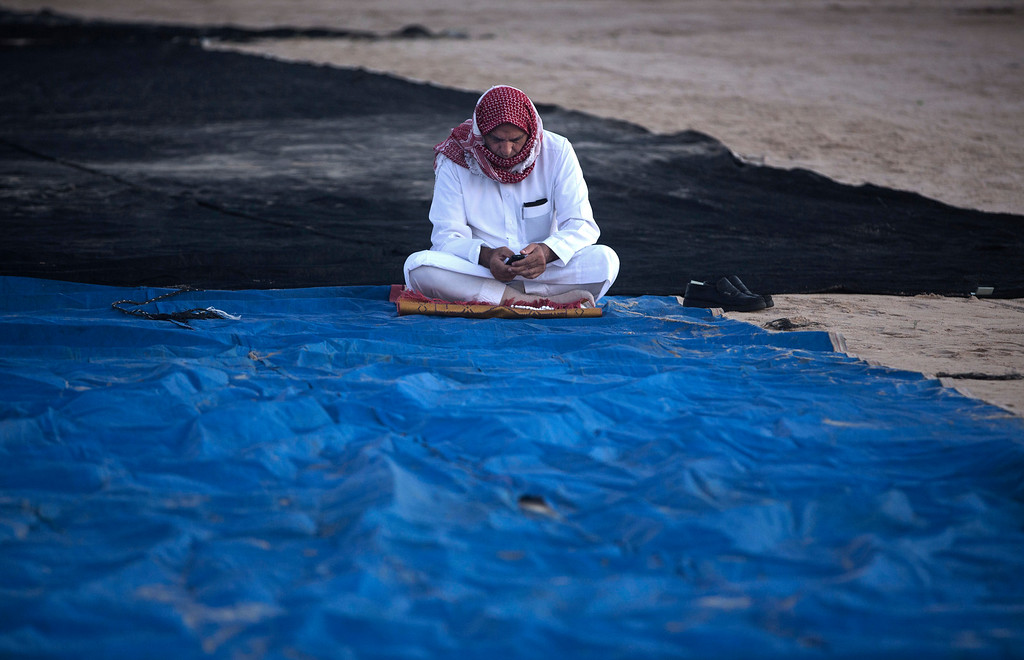 . A Palestinian man sits on the ground waits to preform at Eid al-Fitr prayers, marking the end of the holy fasting month of Ramadan, in Eastern Gaza City, Friday, June 15, 2018. (AP Photo/Khalil Hamra)