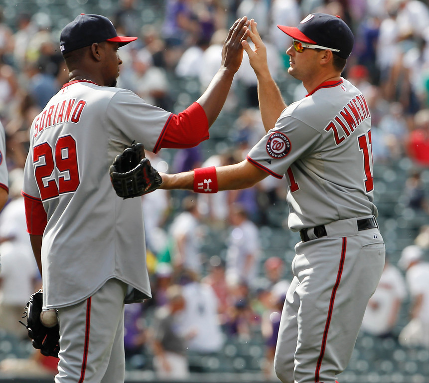 . Washington Nationals relif pitcher Rafael Soriano, left, congratulates third baseman Ryan Zimmerman after their 5-4 victory over the Colorado Rockies in a baseball game in Denver on Thursday, June 13, 2013. (AP Photo/David Zalubowski)