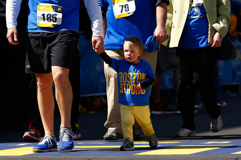 . A young boy crosses the Boston Marathon finish line wearing a \'Boston Strong\' t-shirt during the B.A.A. Tribute Run on April 19, 2014 in Boston, Massachusetts.  (Photo by Jared Wickerham/Getty Images)