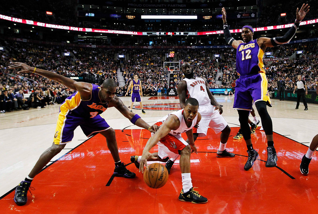 . Toronto Raptors\' Kyle Lowry (center L) and Quincy Acy (center R) battle for the ball with Los Angeles Lakers\' Antawn Jamison (4) and Dwight Howard (12) during the first half of their NBA basketball game in Toronto, January 20, 2013.     REUTERS/Mark Blinch