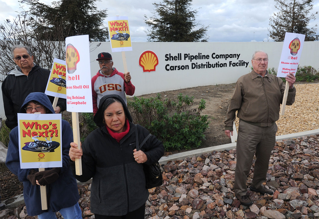 . Residents of the Carousel Tract neighborhood in Carson staged a protest against Shell Oil Friday by marching with signs from Dolphin Park to a Shell facility on Wilmington Avenue.  Protestors stand at the entrance to the Shell facility. 20130308 Photo by Steve McCrank / Staff Photographer