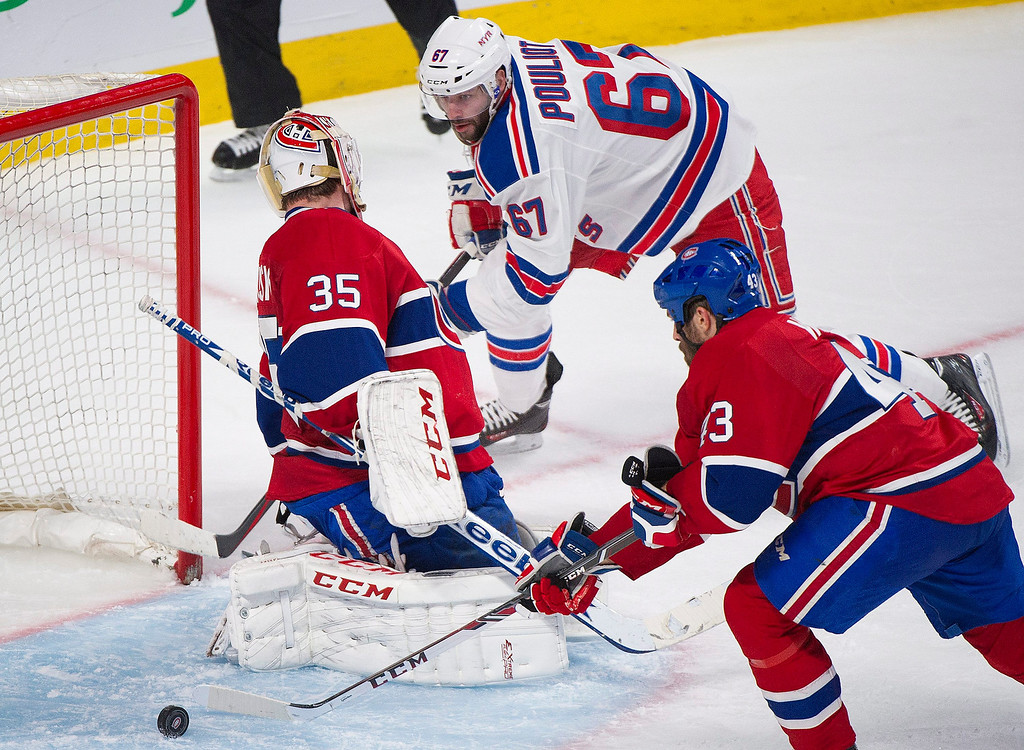 . Montreal Canadiens goaltender Dustin Tokarski, left, loses the puck as New York Rangers\' Benoit Pouliot, right, moves in as Canadiens\' Mike Weaver defends during the third period in Game 2 of the NHL hockey Eastern Conference final Stanley Cup playoff game in Montreal, Monday, May 19, 2014.  (AP Photo/The Canadian Press, Graham Hughes)