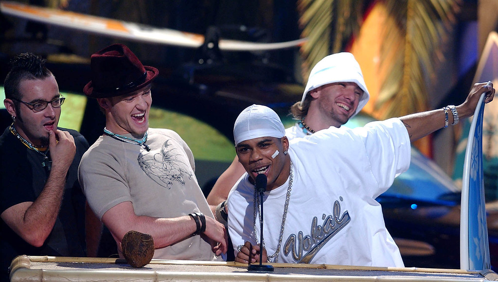 ". Members of \'N Sync, from left, Chris Kirkpatrick, Justin Timberlake, and J.C. Chasez, background right, joke with rap artist Nelly, at microphone, as they accept the award for Choice Single for ""Girlfriend,\"" which features Nelly, Sunday, Aug. 4, 2002, at the Teen Choice Awards 2002 in Los Angeles. (AP Photo/Lucy Nicholson)"
