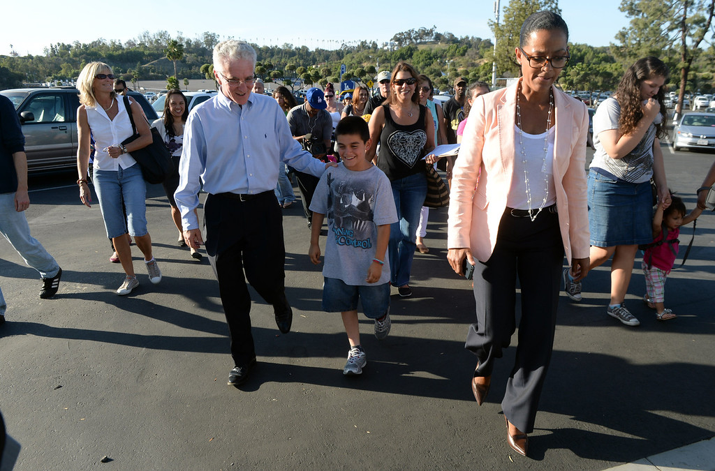 . Los Angeles City Councilmember Paul Krekorian, District 2, left, walks with William and Dodger Senior Vice President External Affairs Renata Simril, right, as they enter the stadium as members of the San Fernando Valley Rescue Mission are treated to a Major league baseball game between the Miami Marlins and the Los Angeles Dodgers on Wednesday, May 14, 2014 in Los Angeles. The Mission experienced a devastating fire earlier this month. Damage sustained included the destruction of the San Fernando Valley Rescue Mission�s emergency shelter, vehicle fleet, clothing warehouse and food pantry which were vital in aiding those of need in the San Fernando Valley.  (Keith Birmingham/Pasadena Star-News)