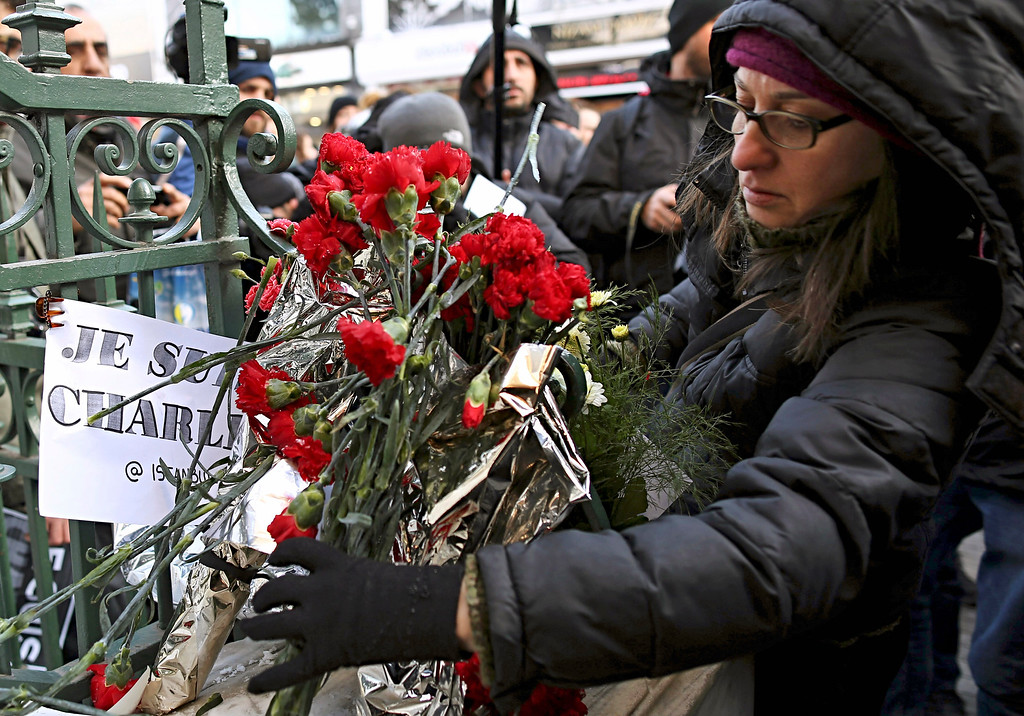 ". People gather outside French consulate to pay tribute to the victims of the French satirical newspaper Charlie Hebdo, in Istanbul, Turkey, Thursday, Jan. 8, 2015. Masked gunmen stormed the Paris offices of a weekly newspaper that caricatured the Prophet Muhammad, killing 12 people, including the editor, before escaping in a car. It was France\'s deadliest postwar terrorist attack. The placard reads ""I am Charlie.\""(AP Photo/Emrah Gurel)"