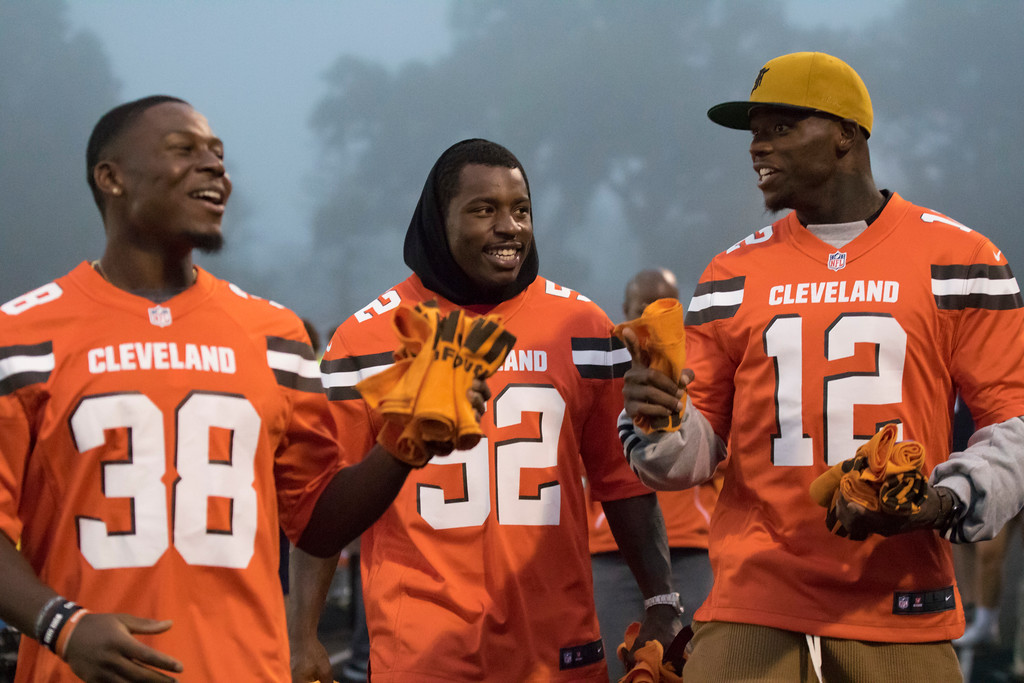 . Jen Forbus - The Morning Journal<br> Cleveland Browns players, from left to right, T.J. Carrie, James Burgess and Josh Gordon prepare to throw Browns towels to the fans in the bleachers on Sept. 14.