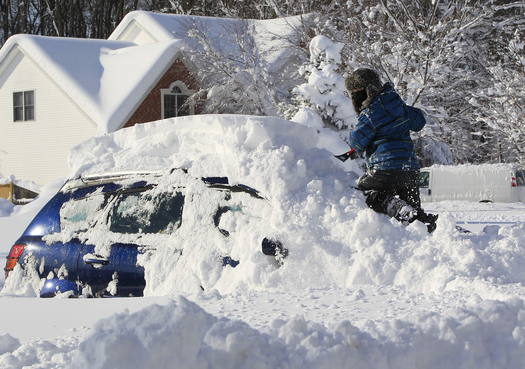 . Braeden Attig,11, removes snow from a buried car along Powers Road in Orchard Park, N.Y. on Wednesday, Nov. 19, 2014.  A ferocious lake-effect storm left the Buffalo area buried under 6 feet of snow Wednesday, trapping people on highways and in homes, and another storm expected to drop 2 to 3 feet more was on its way. (AP Photo/The Buffalo News, Harry Scull Jr.)