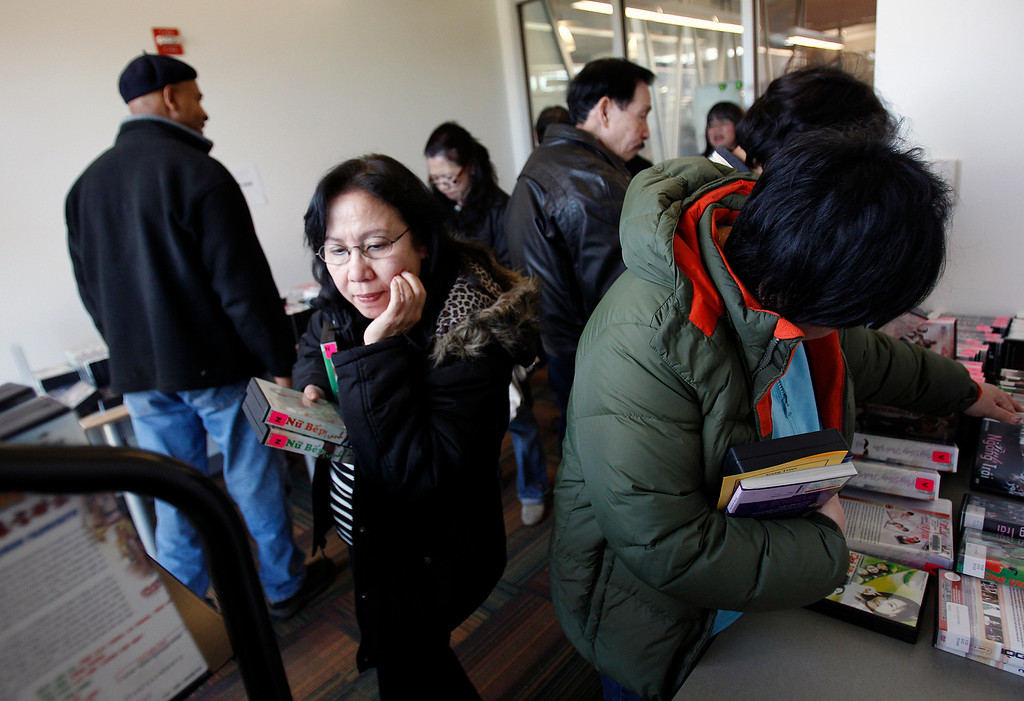 . Patrons borrow Vietnamese movies at the Seven Trees Branch Library after its grand opening celebration, in San Jose, Calif. on Saturday, January 26, 2013.   (LiPo Ching/Staff)