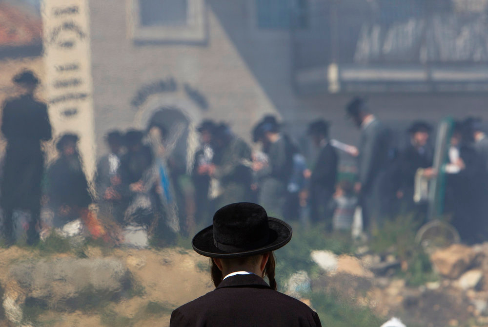 . An ultra-Orthodox Jew is seen through a heat mirage as they burn leaven in the Mea Shearim neighborhood of Jerusalem, ahead of the Jewish holiday of Passover, March 25, 2013. Passover commemorates the flight of Jews from ancient Egypt, as described in the Exodus chapter of the Bible. According to the account, the Jews did not have time to prepare leavened bread before fleeing to the promised land. REUTERS/Ronen Zvulun