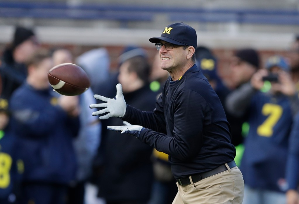 . Michigan head coach Jim Harbaugh catches during warmups before an NCAA college football game against Ohio State, Saturday, Nov. 25, 2017, in Ann Arbor, Mich. (AP Photo/Carlos Osorio)