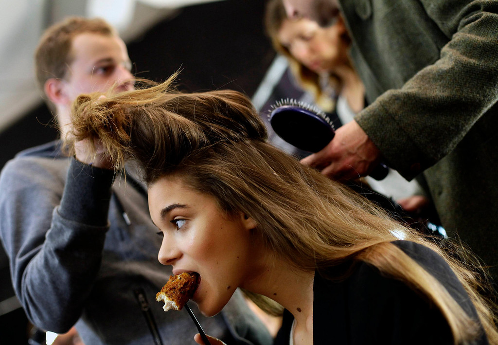 . A model eats a piece of chicken as her hair is styled backstage before the Herve Leger By Max Azria Autumn/Winter 2013 collection runway show during New York Fashion Week February 9, 2013. REUTERS/Joshua Lott