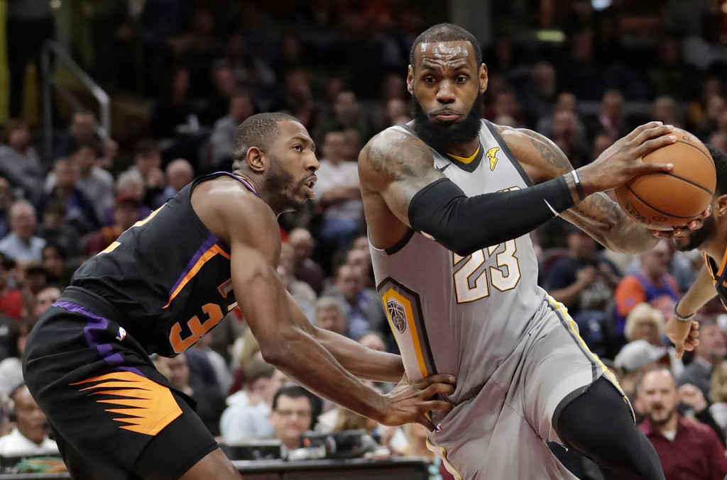 . Cleveland Cavaliers\' LeBron James, right, drives past Phoenix Suns\' Davon Reed during the second half of an NBA basketball game Friday, March 23, 2018, in Cleveland. The Cavaliers won 120-95. (AP Photo/Tony Dejak)
