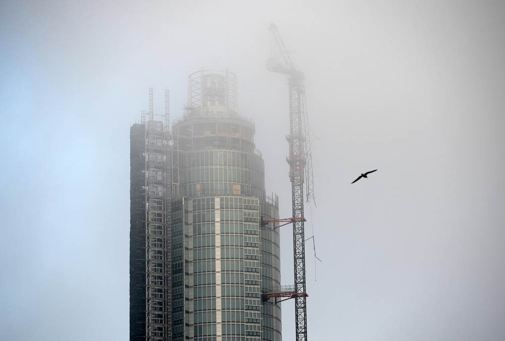 Description of . A bird flies through the mists near the damaged crane on the St George\'s Tower at Vauxhall in London January 16, 2013. A helicopter crashed into a crane on top of one of Europe\'s tallest residential blocks in central London on Wednesday, killing two people as it burst into flames and threw plumes of smoke into the foggy air.  REUTERS/Dylan Martinez