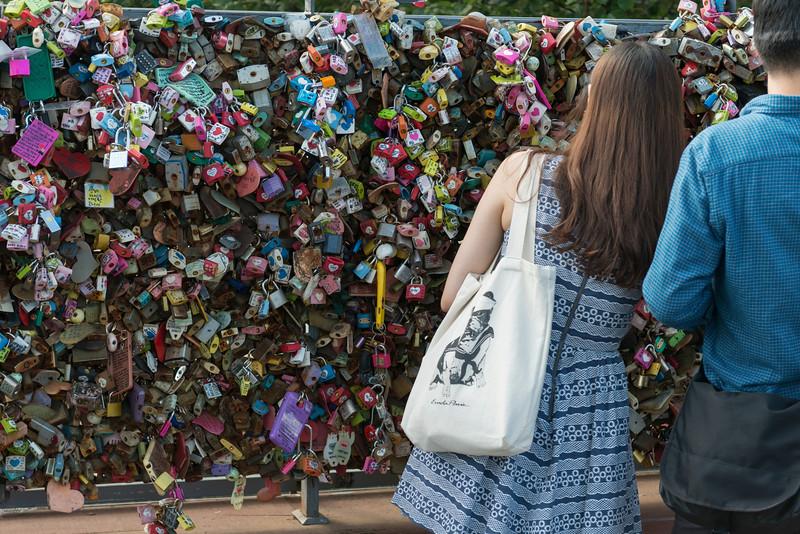 Couple standing near love lock, Namsan Park, Seoul Tower, Seoul, South Korea