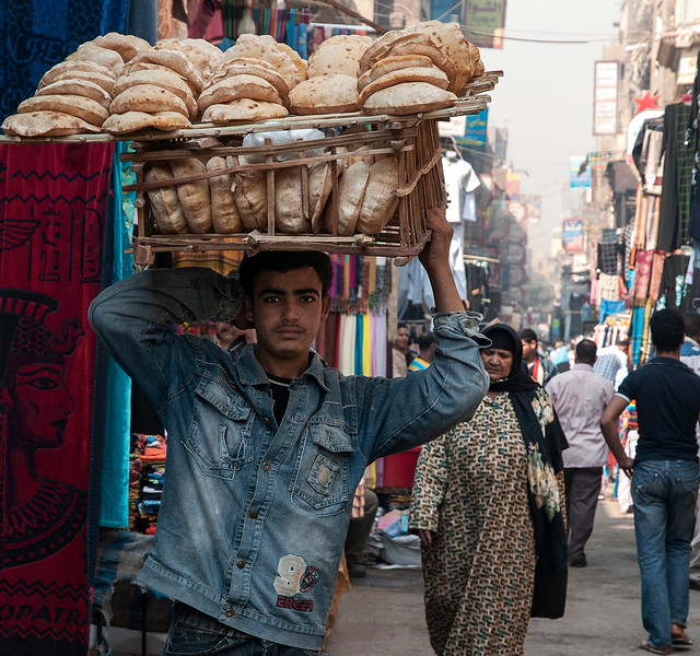Boy wearing eye liner just like the ancient Pharaohs. He is carrying freshly baked bread from the bakery to the local shops. Khan al-Khalili market.   Cairo, Egypt, 2010.