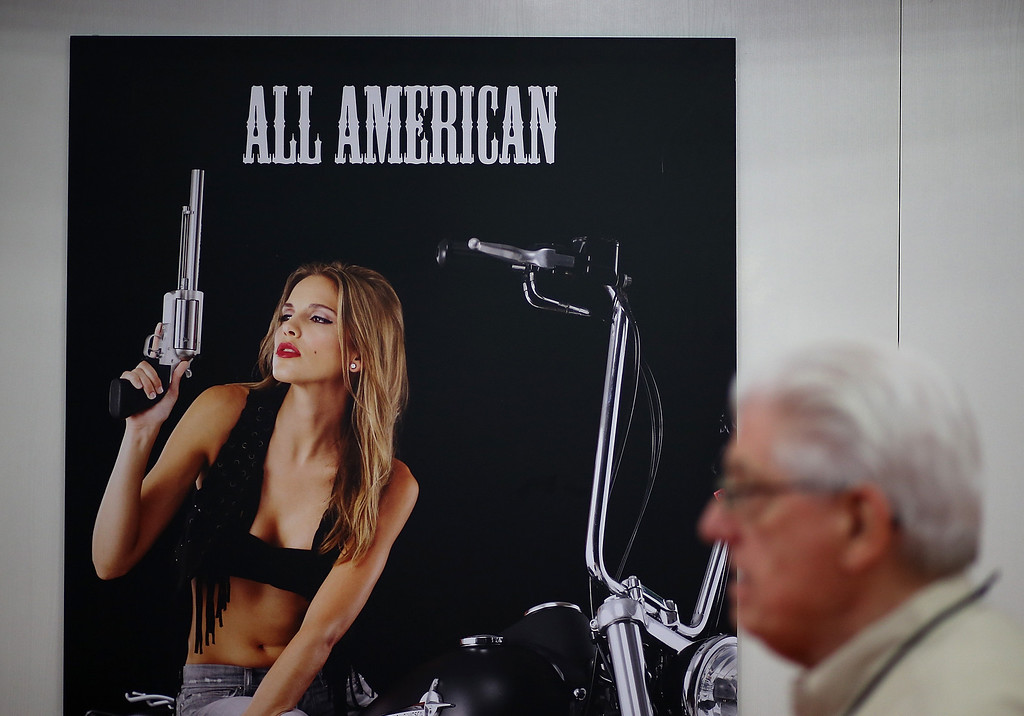 . HOUSTON, TX - MAY 03:  An attendee walks by a poster during the 2013 NRA Annual Meeting and Exhibits at the George R. Brown Convention Center on May 3, 2013 in Houston, Texas.  More than 70,000 peope are expected to attend the NRA\'s 3-day annual meeting that features nearly 550 exhibitors, gun trade show and a political rally. The Show runs from May 3-5.  (Photo by Justin Sullivan/Getty Images)